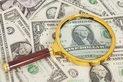 Banconote del dollaro sotto la lente d'ingrandimento Immagini Stock Libere da Diritti