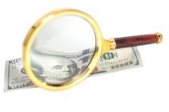 Banconote del dollaro sotto la lente d'ingrandimento Fotografie Stock Libere da Diritti