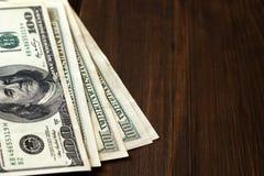 Banconote del dollaro su fondo di legno scuro con lo spazio della copia Immagini Stock