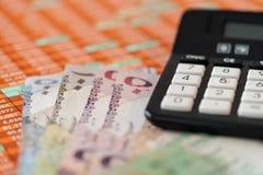 Banconote del riyal del Qatar sul fondo di rapporto del foglio elettronico con il calcolatore fotografia stock