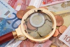 Banconote dell'euro e della lente d'ingrandimento con le monete Fotografia Stock Libera da Diritti
