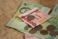 Banconote di baht della Tailandia con le monete di baht della Tailandia Fotografia Stock