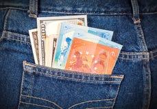 Banconote differenti dell'euro e della valuta americana che attaccano fuori Fotografia Stock
