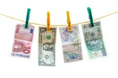 Banconote differenti di valuta che appendono sulla corda da bucato Fotografia Stock