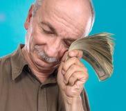 Banconote in dollari anziane fortunate della tenuta dell'uomo Fotografia Stock