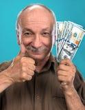Banconote in dollari anziane fortunate della tenuta dell'uomo Fotografia Stock Libera da Diritti