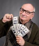Banconote in dollari anziane fortunate della tenuta dell'uomo Immagini Stock Libere da Diritti
