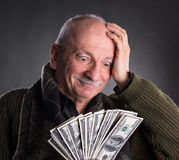 Banconote in dollari anziane fortunate della tenuta dell'uomo Fotografie Stock Libere da Diritti
