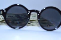 100 banconote in dollari attraverso gli occhiali di protezione del sole fotografia stock