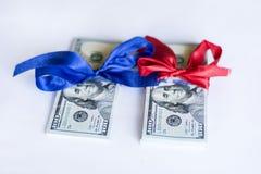100 banconote in dollari con il nastro rosso e blu su un fondo bianco Fotografie Stock