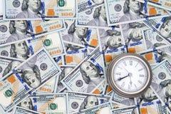 Banconote in dollari dell'americano 100 con un orologio d'annata Fotografia Stock