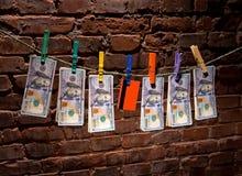 Banconote in dollari e carta di credito che appende su una corda Fotografie Stock Libere da Diritti