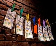 Banconote in dollari e carta di credito che appende su una corda Immagine Stock