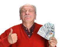 Banconote in dollari fortunate della tenuta dell'uomo anziano Fotografia Stock Libera da Diritti