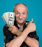 Banconote in dollari fortunate della tenuta dell'uomo anziano Fotografie Stock Libere da Diritti