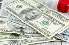 Banconote in dollari impilate e un grande cubo rosso Fotografia Stock Libera da Diritti