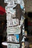 Banconote in dollari lacerate e nocive cucite con punti metallici ad una posta di legno fotografia stock