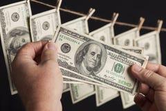Banconote in dollari maschii della tenuta cento, molte che passano dalla corda da bucato Fotografia Stock Libera da Diritti