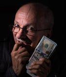 Banconote in dollari sleali della tenuta dell'uomo senior Fotografie Stock Libere da Diritti