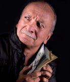 Banconote in dollari sleali della tenuta dell'uomo senior Immagini Stock Libere da Diritti