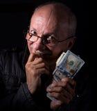 Banconote in dollari sleali della tenuta dell'uomo senior Immagine Stock
