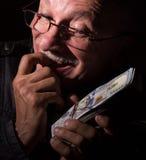 Banconote in dollari sleali della tenuta dell'uomo senior Fotografia Stock