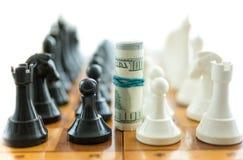 Banconote in dollari torte fra i pezzi degli scacchi bianchi e neri Immagine Stock Libera da Diritti