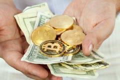 Banconote e bitcoins in mani maschii Immagini Stock