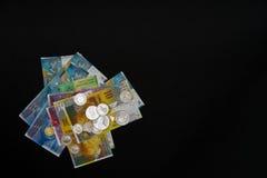 Banconote e monete che si trovano su a vicenda su fondo nero Immagini Stock Libere da Diritti
