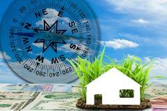 Banconote euro e dollari con la casa sul giovane growi dell'erba verde Immagine Stock