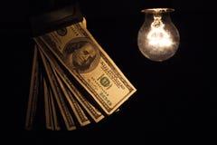 Banconote illuminanti d'attaccatura della lampadina Fotografia Stock