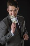 Banconote mordaci del dollaro dell'uomo d'affari isolate sul nero Fotografia Stock Libera da Diritti