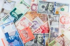 Banconote multiple di valute come fondo variopinto Fotografia Stock