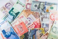 Banconote multiple di valute come fondo variopinto Immagine Stock