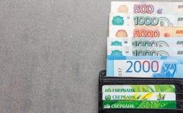 Banconote russe nelle denominazioni di 1000, 2000 e 5000 rubli e carte di credito Sberbank in un primo piano di cuoio nero della  Immagine Stock