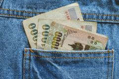 Banconote, soldi tailandesi di valuta di 1.000 baht dietro al blu della tasca Fotografia Stock