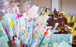 Banconote tailandesi nella tradizione di carità di buddismo Immagini Stock Libere da Diritti