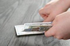 Banconote teenager femminili del dollaro della tenuta della mano Immagini Stock