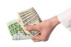 Banconote umane della holding della mano (euro e dollaro) Fotografie Stock