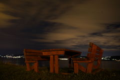 Bancos com a tabela na noite Foto de Stock Royalty Free