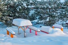 Bancos con la tabla en la nieve Imágenes de archivo libres de regalías