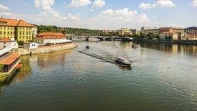 Bancos da vista do rio de Vltava, de barcos de turista e da ponte de Manesuv no centro histórico de Praga, República Checa fotos de stock royalty free