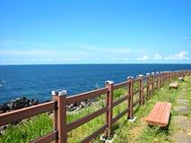 Bancos de madeira ao longo da costa do mar no verão fotografia de stock