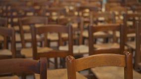 Bancos de madeira na igreja Católica Fileiras de cadeiras de madeira marrons no templo Nenhuns povos em torno do salão vazio video estoque