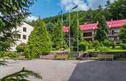 Bancos de madera cómodos, una fuente de la piedra decorativa y abetos altos en la entrada al edificio del hotel con a Foto de archivo libre de regalías
