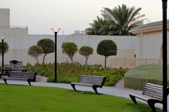 Bancos de parque, calzada, arbustos Imagen de archivo libre de regalías