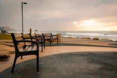Bancos de parque de la ciudad por el océano - puesta del sol Foto de archivo libre de regalías