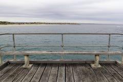 Bancos e assentos no molhe de Noarlunga do porto com a praia no backgrou imagens de stock