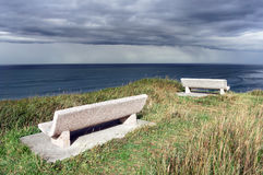 Bancos en el acantilado cerca del mar con las nubes tempestuosas Fotos de archivo libres de regalías