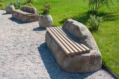 Bancos feitos da pedra e da madeira no parque fotografia de stock